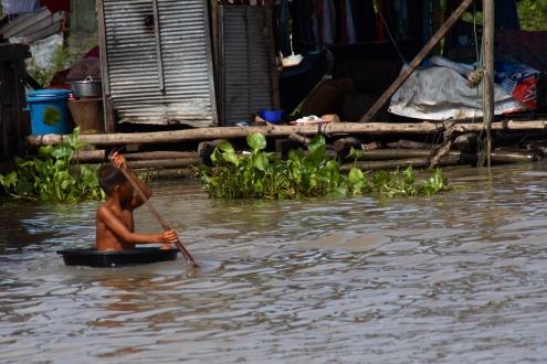 Un pequeño marinero del Tonlé Sap hace su aparición e intenta llegar a una motora de turistas.