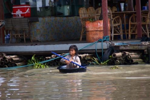 Este pequeño marinero del Tonlé Sap se afana en llegar a una motora de turistas.