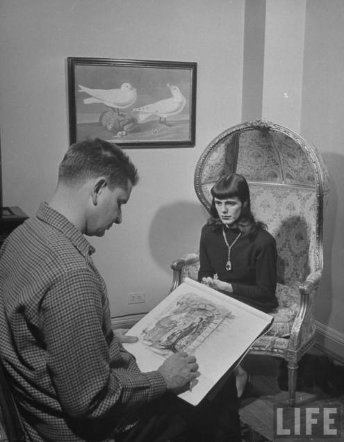 Cartoonist Charles Addams using a model for his cartoon