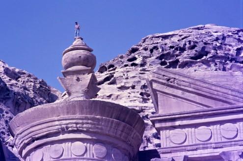 A la izquierda de la fachada, a través de una pequeña abertura en la roca, hay una tosca escalera que lleva hasta el borde de la urna que hay arriba.